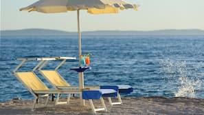 Plage, sable blanc, chaises longues, serviettes de plage