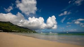 På stranden, solsenger, strandhåndklær og strandyoga