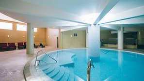 Una piscina cubierta, una piscina al aire libre, tumbonas