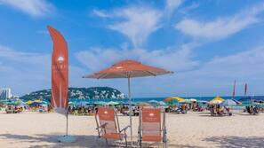 Nära stranden, solstolar, parasoller och strandhanddukar