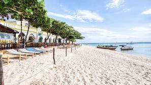 Na praia, areia branca, serviço de traslado de/para a praia
