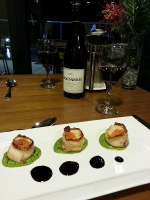 Pan seared scallops wrapped in spanish jamon on pea puree, salmon pearls, and with a sticky balsamic