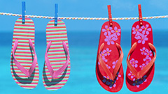 2 pairs of flip flops hanging on a clothesline