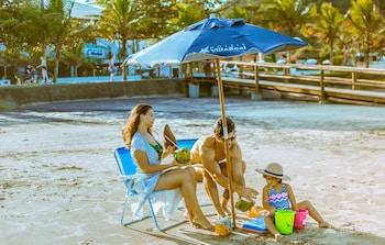 Na praia, guarda-sóis, toalhas de praia